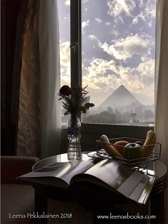 Reading a book with a view to the pyramids of Giza through the window.